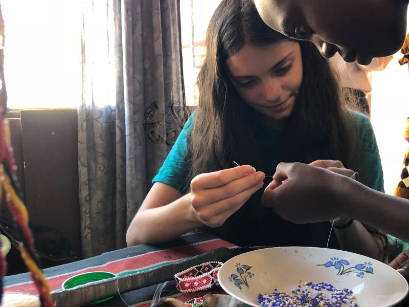 Maya helps create African jewelry with beads which will be donated